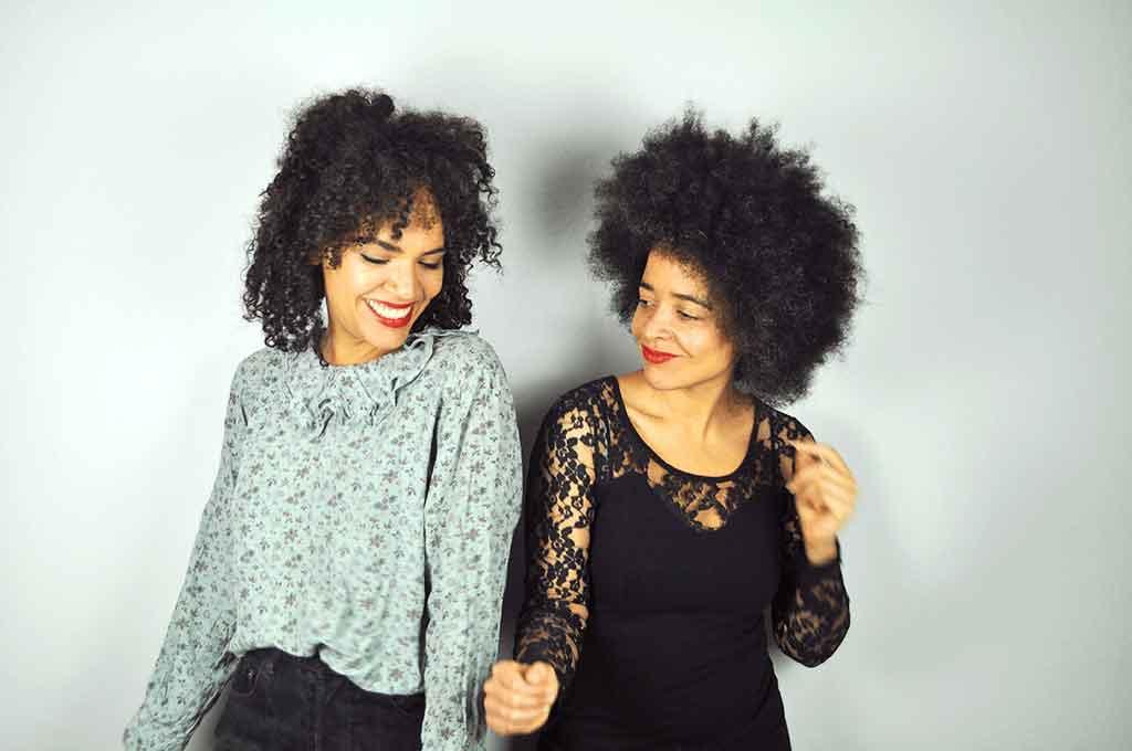 Zwei Frauen tanzen vor einer grauen Wand und lächeln.