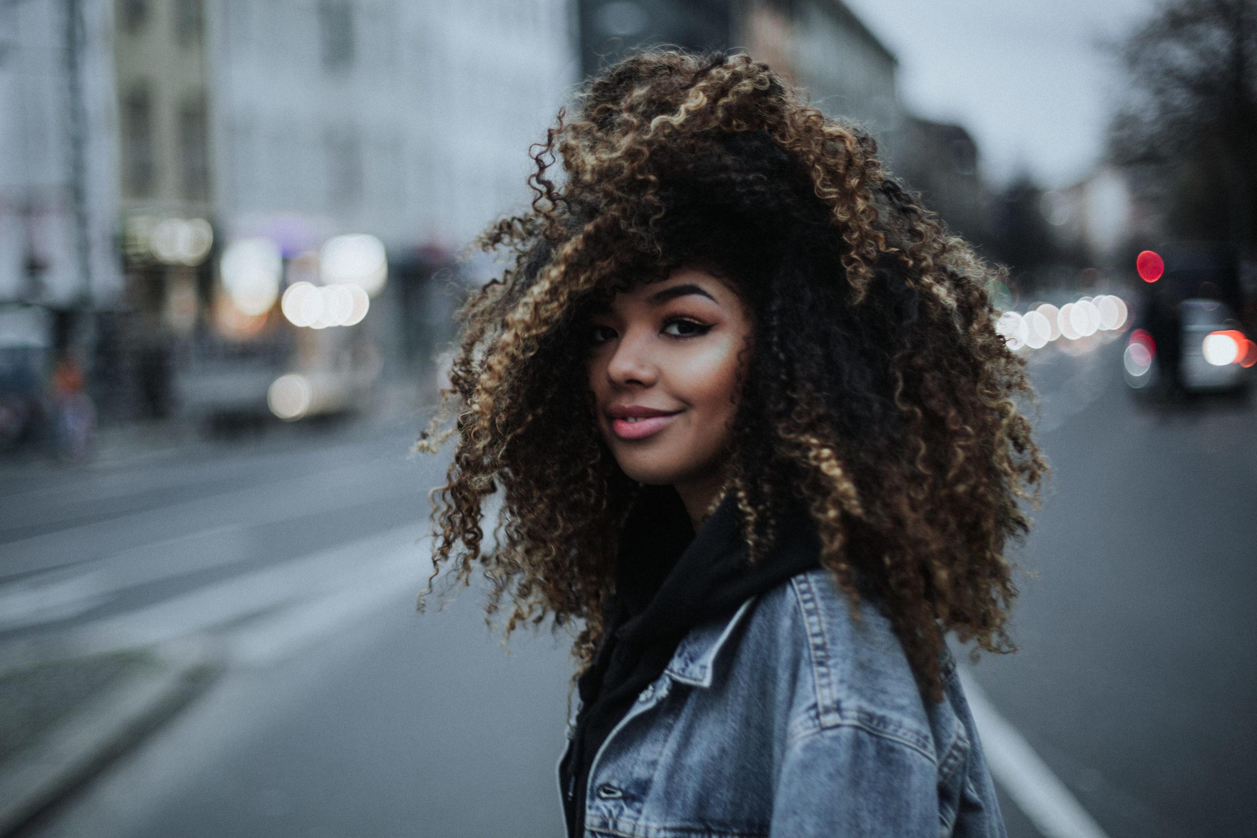 Die Sängerin und Rapperin Gini auf der Straße, lächelt in die Kamera.
